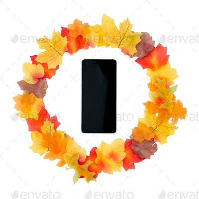 Autumn Still Life Of Leaves And Pine Cones Arranged A Circle Around Mobile Phone On White Background