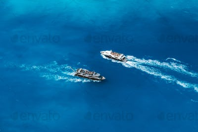 Fully occupied tourist boats in open sea on trip to the world most famous Navagio Beach on Zakynthos