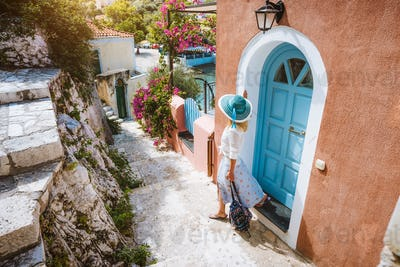 Summer vacation holiday. Travel tourist woman on vacation in Greece. Traditional Mediterranean house