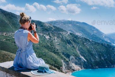 Adult female tourist with camera enjoying seascape of Kefalonia, Greece on summer holiday vacation