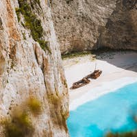 Close up of Navagio beach called Shipwreck bay. Turquoise water and pebble white beach and limestone