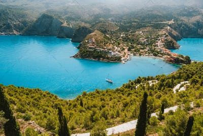 Top view to Assos village. Landmark place of Kefalonia island. Lonely white yacht at anchor in calm