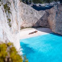 Shipwreck on Navagio beach. Azure turquoise sea water and paradise sandy beach. Famous tourist
