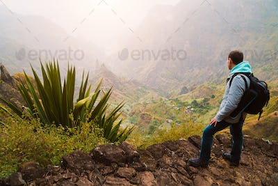 Active vacation at Santo Antao Island, Cape Verde. Traveler with backpack on hike enjoying view of
