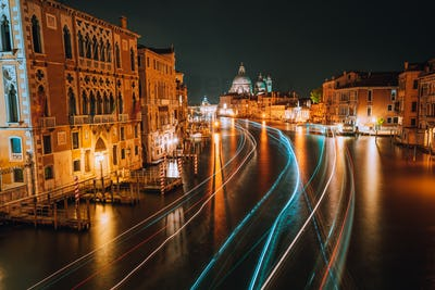 Venice twilight blue night scenery. Light illuminated trails of ferries and boats reflected on the