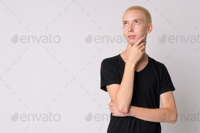 Portrait of young happy androgynous man thinking