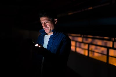 Suspicious-looking Hispanic man using phone in dark parking lot