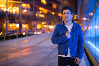 Hispanic man exploring the city streets at night