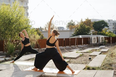 Two young girls practicing stretching and yoga workout exercise together