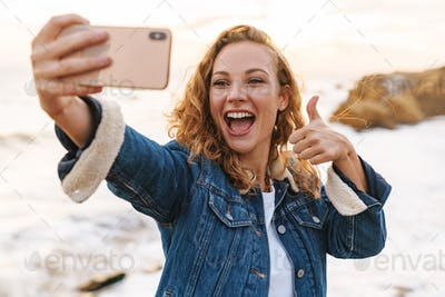 Image of young beautiful woman using smartphone while walking by seaside