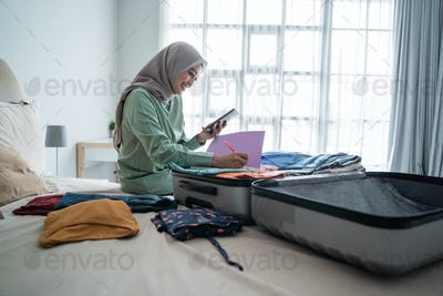 hijab woman sitting on the bed while looking at the list of items