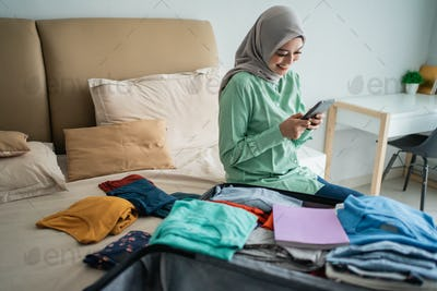 asian muslim woman looking departure schedules via mobile phone