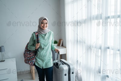 beauty young hijab traveler walk and carrying her bag and holding suitcase
