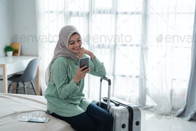 young asian woman sitting on the bed holding her handphone and suitcase