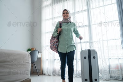smiling young hijab traveler carrying her bag and holding suitcase