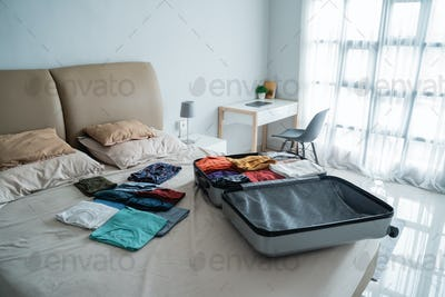 suitcase with lots of clothes on the bed