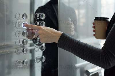 Hand of young businesswoman with drink pushing button of elevator