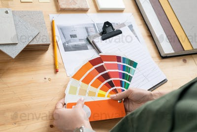 Hands of young female designer of interior holding color palette over desk