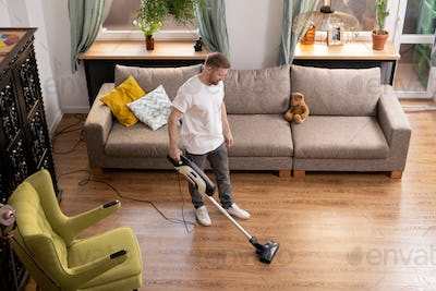 Young man doing domestic work while cleaning floor with vacuum cleaner