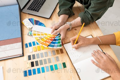 One of female designers holding color palette while her colleague making notes