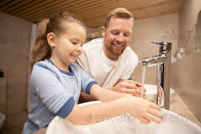 Happy young man looking at his cute little smiling daughter washing hands