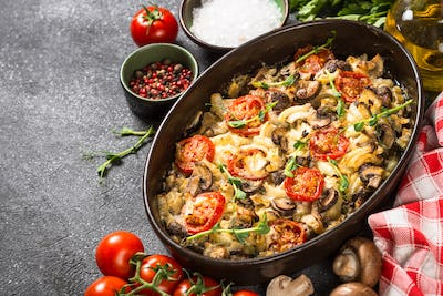 Baked meat with vegetables on black table