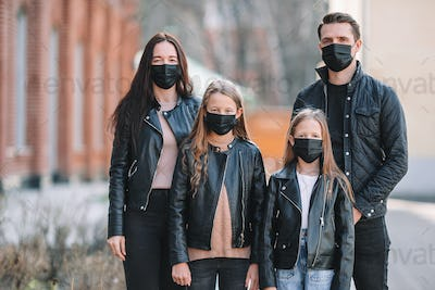 Family wearing a mask on a background of a modern building