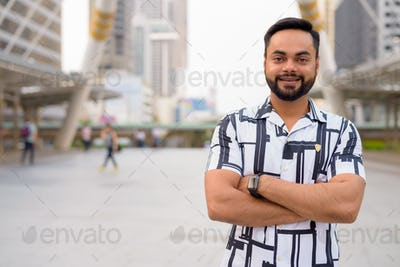 Happy young bearded Indian man with arms crossed in the city outdoors