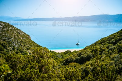 Stunning view of Fteri beach with white sailboat in hidden bay, Kefalonia, Greece. Surrounded by