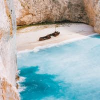 Navagio beach with turquoise blue sea water surrounded by huge white limestone cliffs. Famous