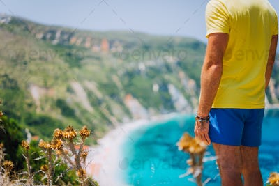 Young male staying in front of Petani beach on Kefalonia. Highly excited picturesque panorama of