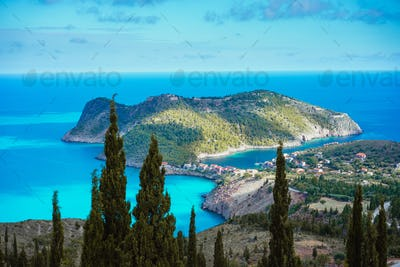 Assos village and coastline of beautiful blue sea. Cypress trees in foreground. Kefalonia island