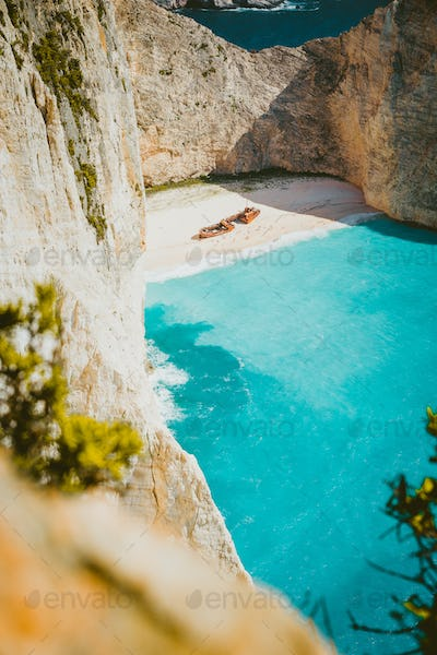 Vertical shot of shipwreck on Navagio beach with turquoise blue sea water surrounded by huge white