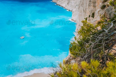 Lonely catamaran yacht in blue bay of Navagio beach. Azure turquoise sea water pattern near paradise