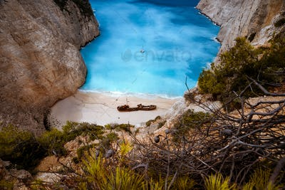 Shipwreck in Navagio beach. Azure turquoise sea water surrounded by huge rocks. Famous tourist