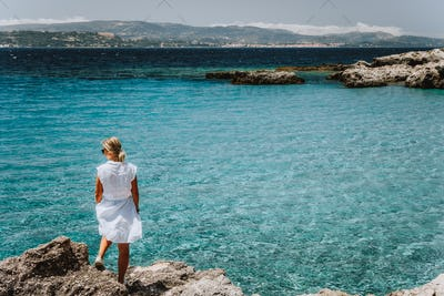 Adult female in white dress on summer vacation enjoying sea coast landscape of small beach with