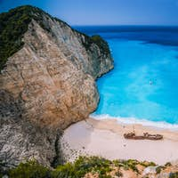 Shipwreck in Navagio beach. Azure turquoise sea water and sandy beach. Famous tourist visiting
