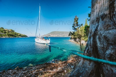 Sail boat on rope in emerald hidden lagoon among picturesque mediterranean nature Ionian Islands