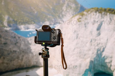 Digital photo camera on tripod against huge cliff rocks of Navagio beach in morning sun light