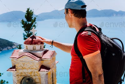 Male tourist touches thoughtful to small Hellenic shrine Proskinitari, Greece. Amazing sea view in