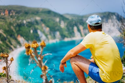 Young male enjoys Petani beach on Kefalonia. Highly excited picturesque panorama of emerald blue