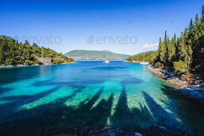 Beautiful Phoki Beach surrounded by cypress trees in the evening sunlight. Amazing seascape of