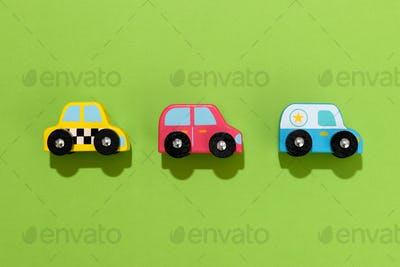 Three colorful wooden toy cars on green background