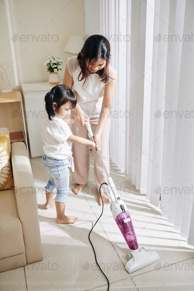 Mother and daughter vacuum cleanning