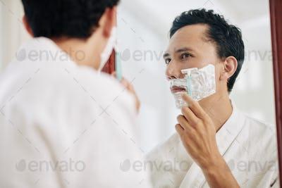 Shaving mixed-race man