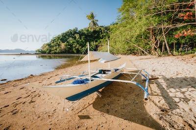 Bangka boat on sandy remote beach with golden sunset light. El Nido bay. Philippines