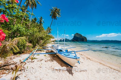 The Philippines's Banca boat. Traditional fishing boat on beach in noon bright sun. El Nido