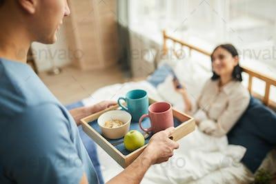 Man bringing Breakfast in Bed