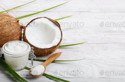 Coconut oil in airtight glass jar spoon and shell pieces on white wooden table