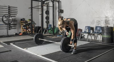 Young strong woman loading weights onto a barbell in a gym.